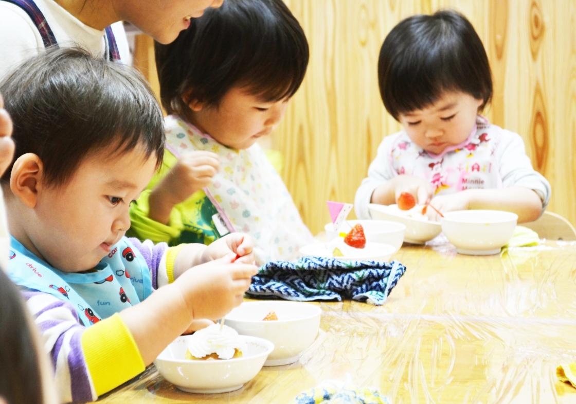子ども達が好きな果物を選んでカップケーキに盛り付け、保育スタッフはその様子を見守ります。