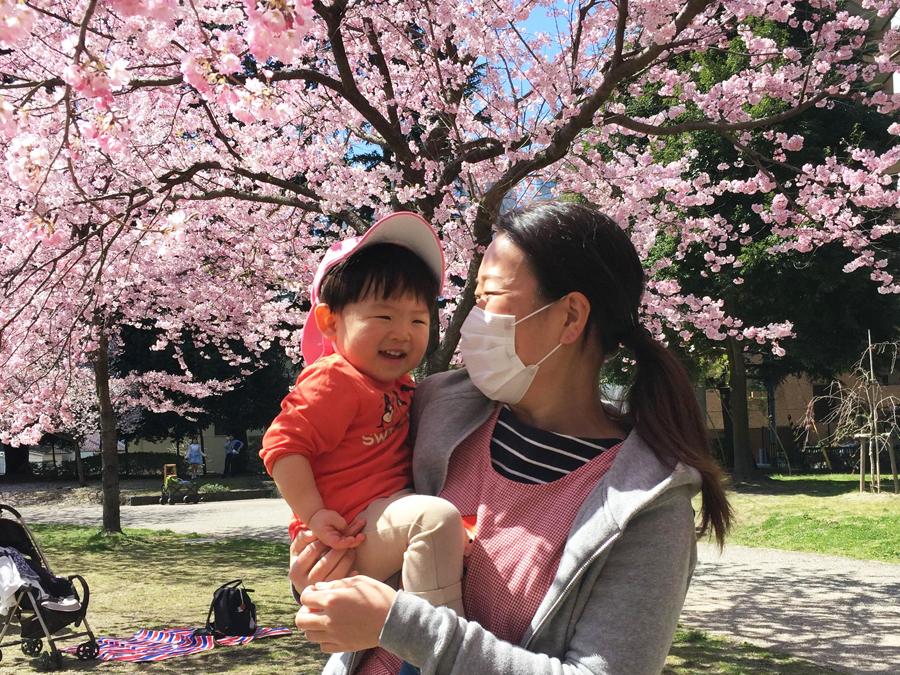 桜の下でお子さんと先生が笑顔の写真