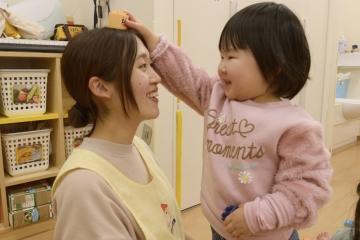 子供と先生が笑顔で遊んでいる様子