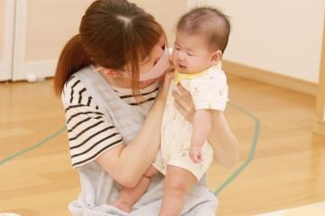 先生が赤ちゃんを抱っこしている写真