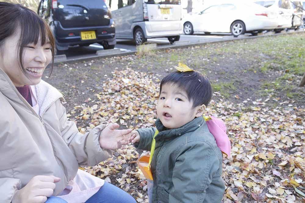 お子さんと先生が葉っぱで遊んでいる写真