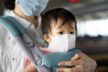 Asian baby with mother in baby carry,baby is wearing a protection mask against air pollution and Wuhan corona covid-19  virus before flight in terminal DonMuang airport,Bangkok, Thailand.